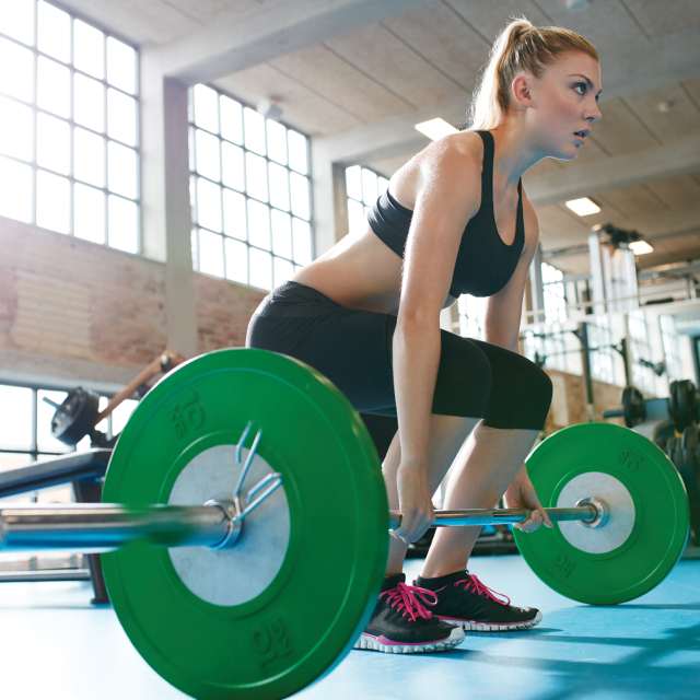 Young Woman lifting a barbell
