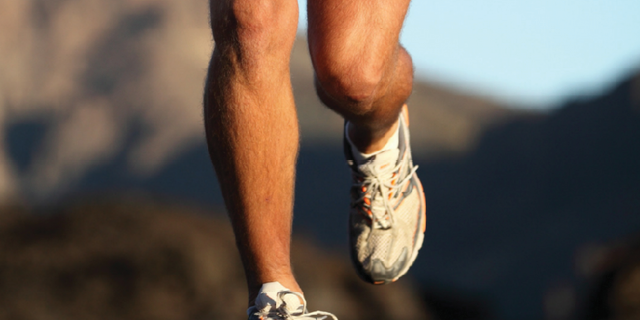 View of male legs jogging toward the camera on a quiet road
